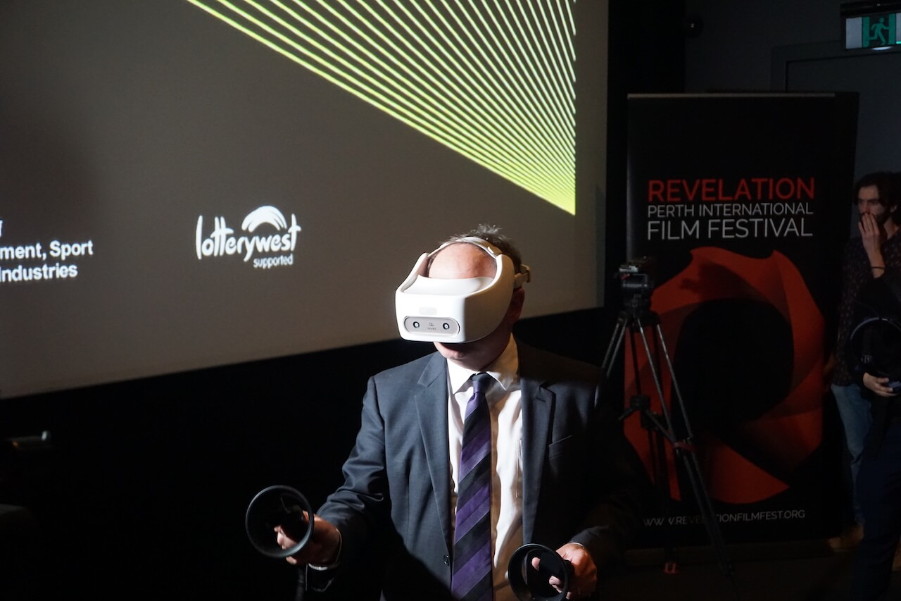 Man wearing VR headset in front of cinema screen