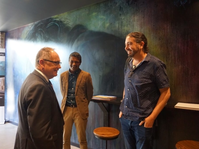3 people talking in front of art-covered wall