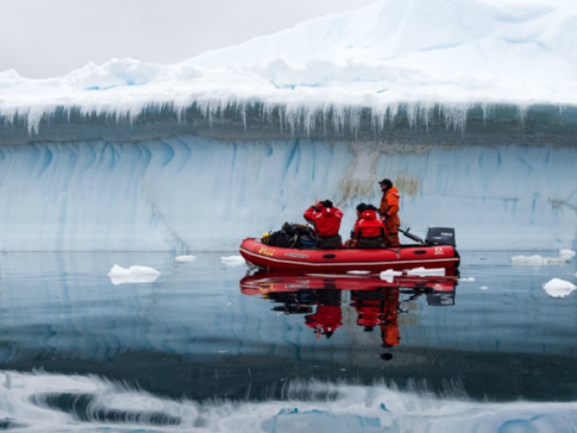 People in a boat surrounded by ice